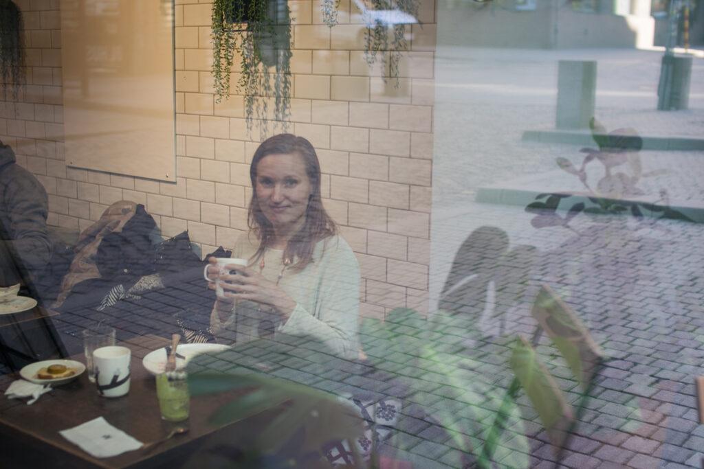 marianne katsoo kameraan ikkunan läpi kahvilassa istuessaan