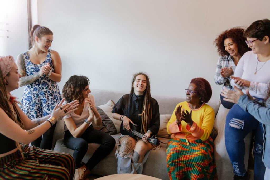 kuvassa seitsemän naista laulavat ja yksi soittaa keskellä kitaraa