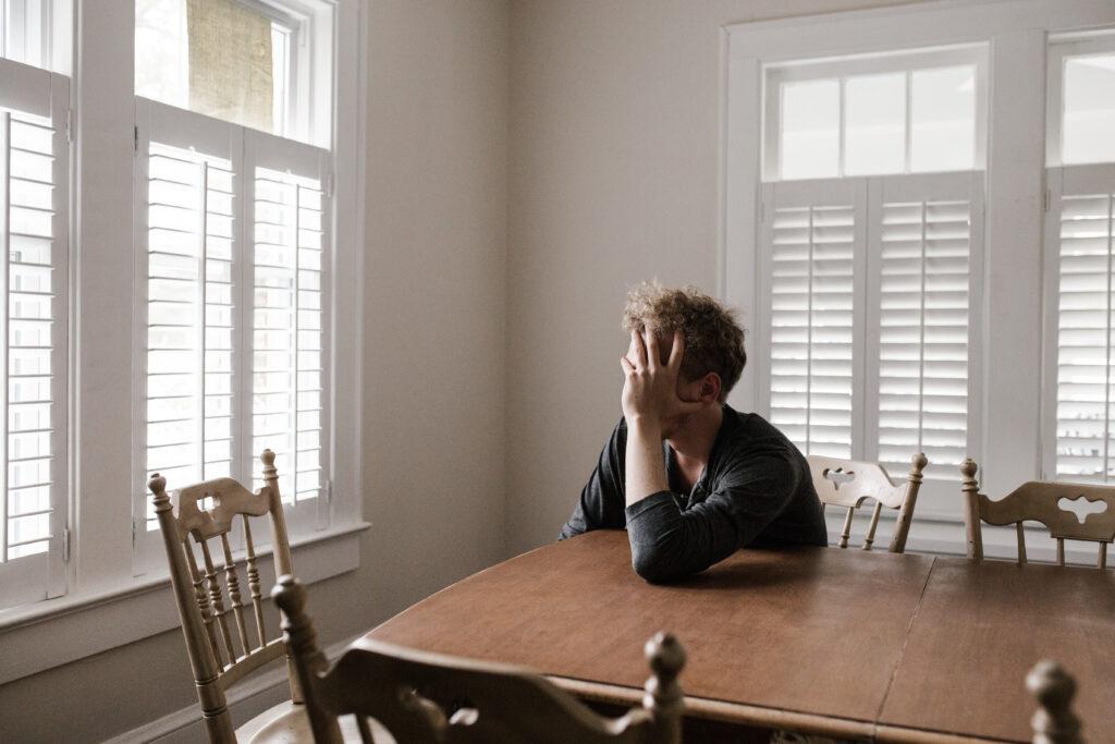 mies istuu pöydän ääressä, nojaa käteensä peittäen kasvonsa