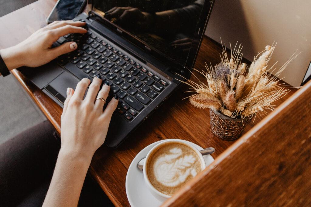kuvassa tietokone ja cappucino